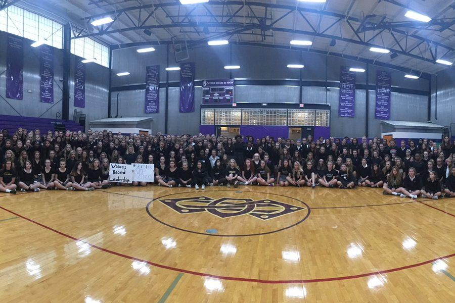 Students gather early in the gym Wednesday morning to take a picture in their black shirts to show their solidarity with the victim.