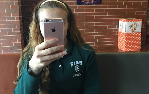 Senior Geneva Sinkula spends time on her iPhone 6 during her study hall.