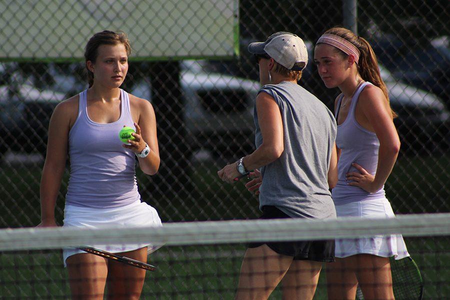 Assistant Coach Karen Phillips gives senior Zoé Trouvé and junior Lanie Jones some tips during their doubles match.