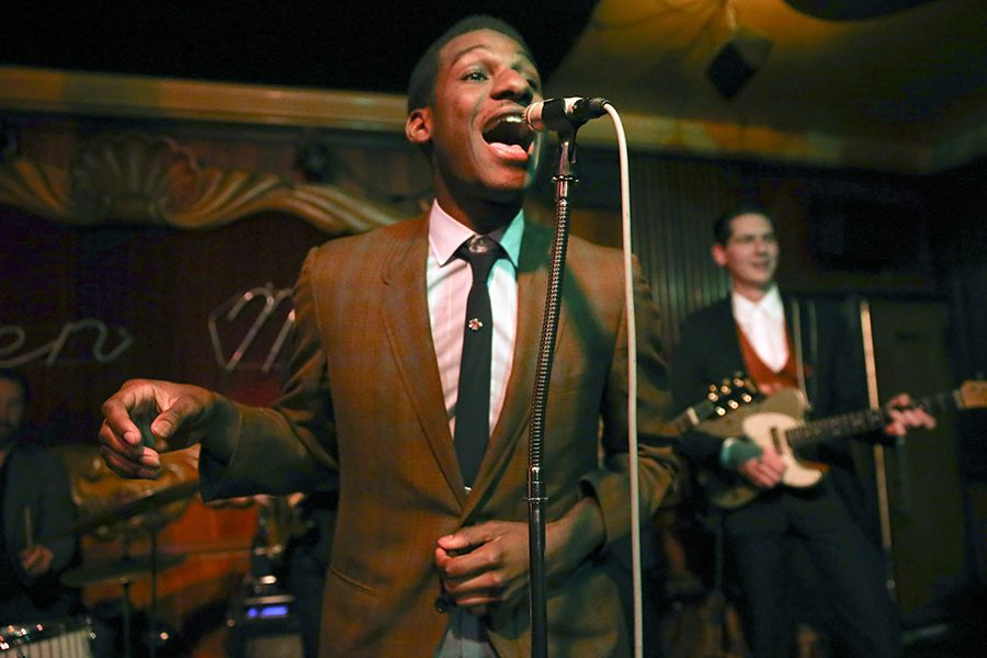 Leon Bridges wears his signature look, a semi-formal vintage suit, while performing with his band.