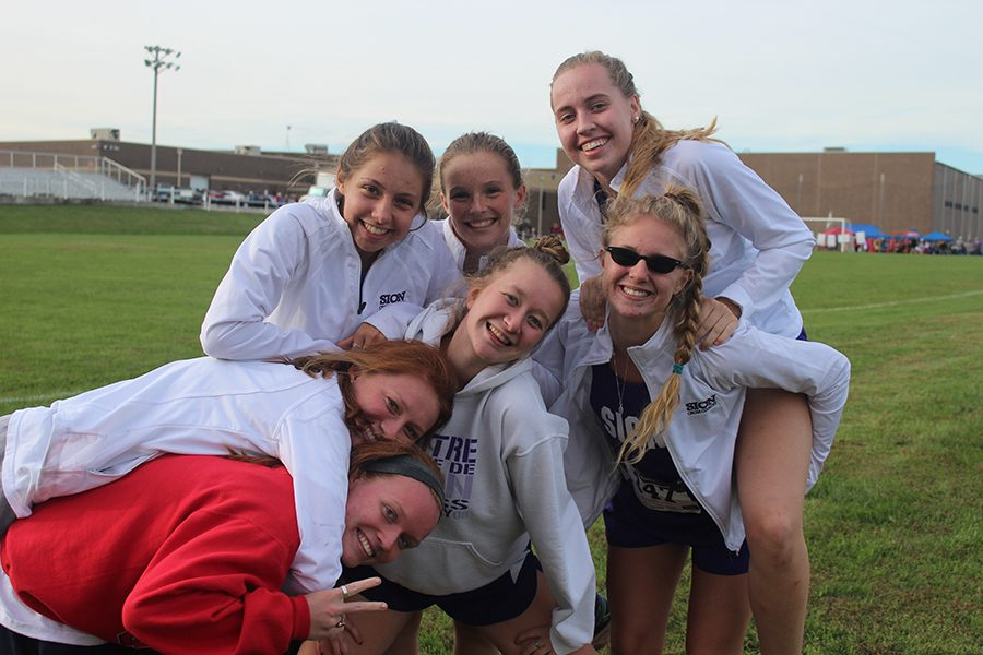 Seniors Nora Malone, Kameron Koppers, Katie Buhrmeister, sophomore Molly Conway, junior Olivia Dopheide and seniors Katia Hauptmann and Clare Kimmis hang out together after one of the last few cross country meets, the Warrensburg Invitational.