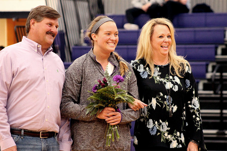 During volleyball senior night, senior Caroline Mollerus walks with her parents after receiving flowers from underclassmen Oct.11.