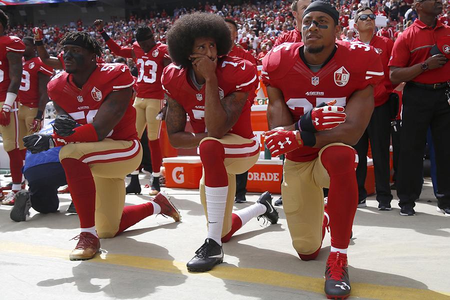San Francisco 49ers' Eli Harold, quarterback Colin Kaepernick and Eric Reid kneel during the national anthem before their NFL game against the Dallas Cowboys Sunday, Oct. 2, 2016 in Santa Clara, Calif.