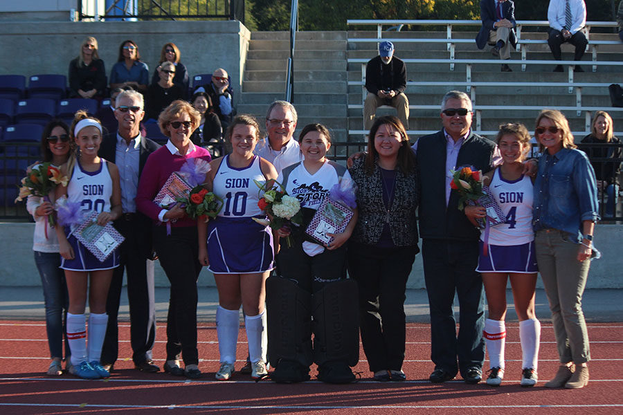 Seniors Mandy Mayer, Grace Frame, Gillian Cruz and Eden Griffith pose for a picture after receiving gifts and flowers at field hockey senior night Oct. 17.