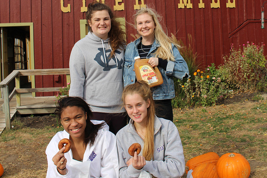 Junior Kaitlin Jones and seniors Kelly Nugent, Phylicia Barner-Lewis and Anna Tomka pose for a picture holding donuts and cider.