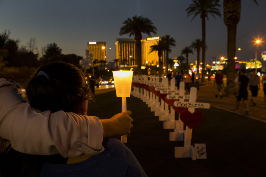 With+wooden+crosses+bearing+the+names+of+those+killed+in+the+mass+shooting%2C+community+members+gather+with+candles+to+pay+tribute+to+their+loss+on+the+median+off+Las+Vegas+Boulevard+on+October+5%2C+2017++in+Las+Vegas%2C+Nevada.+Mandalay+Bay+is+in+the+background.+Greg+Zanis+of+Illinois+drove+all+night+to+deliver+the+homemade+crosses.+%28Gina+Ferazzi+%2F+Los+Angeles+Times%2FTNS%29