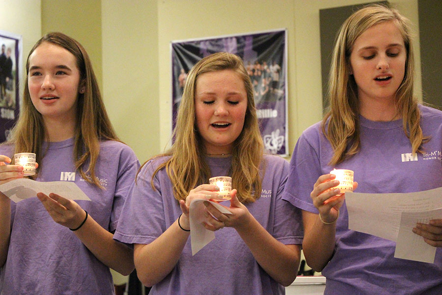 Sophomores Peyton Wade, Avery Kuhls and Emma Hutchin hold candles while performing a song at the Tri-M recital Nov. 14.