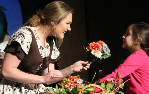 "Sophomore Avery Kuhls, playing Cinderella, offers flowers to a Gabrielle Aguayo on stage during the musical ""Cinderella,"" performed Jan. 19-21."