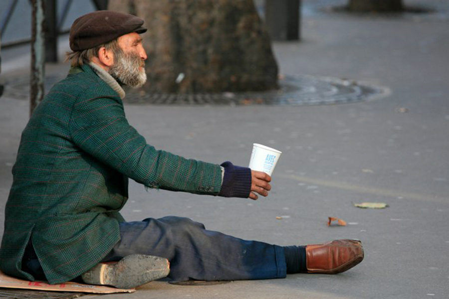 A+man+sits+on+a+piece+of+cardboard+in+Paris%2C+France+with+nothing+but+the+clothes+he+is+wearing+and+a+cup+to+collect+change+in.