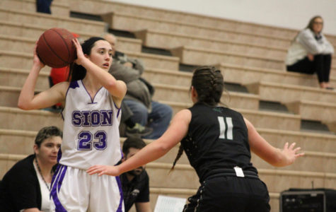 Senior guard Meghan Frerking aims to pass the ball over Staley senior Lindsey Gilbert. Sion went on to defeat Staley at the Blue Valley North varsity basketball tournament 45-33 Friday, Jan 19.