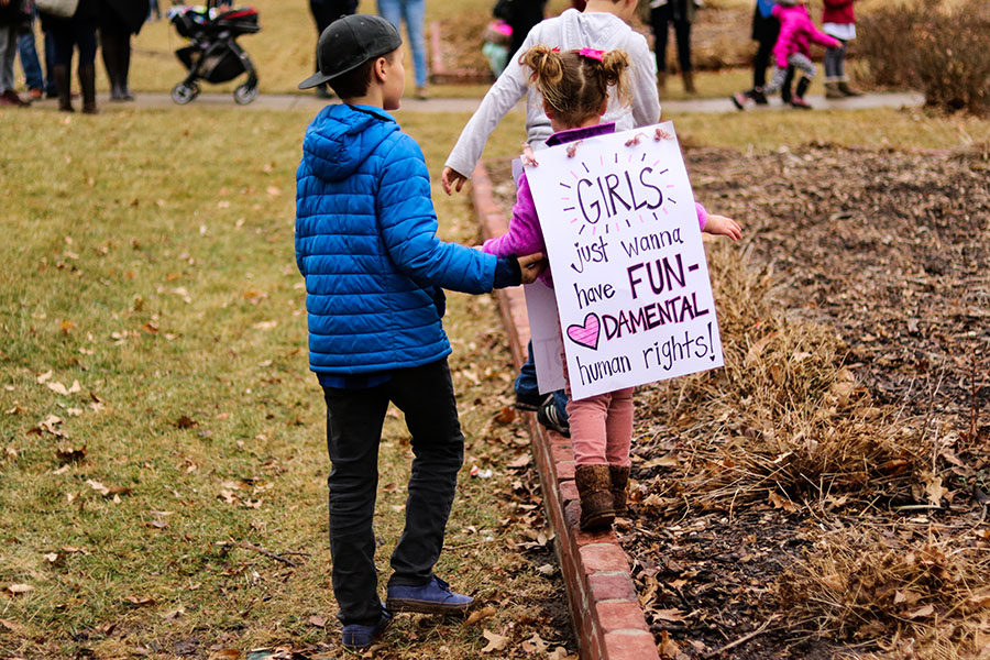 A little girl walks on brick while holding her holder brother's hand at the Women's March in Lawrence, Kansas Jan. 20.