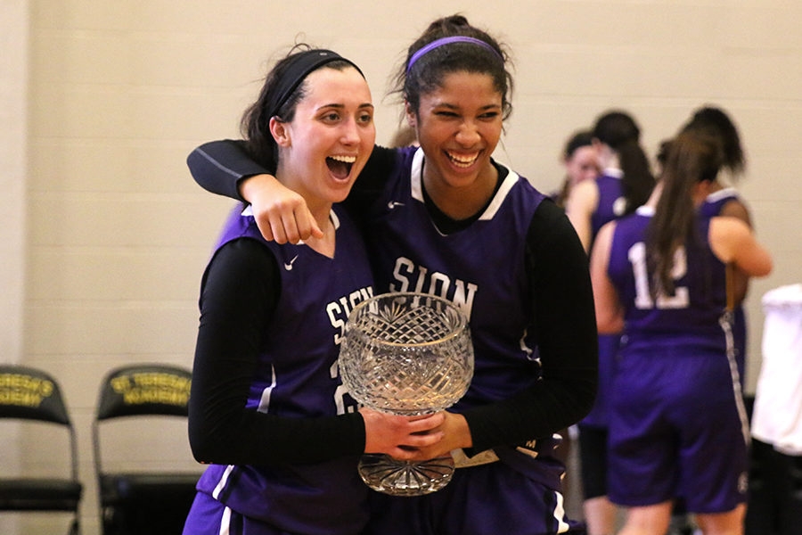 After beating St. Teresa's Academy 50-42, seniors Meghan Frerking and Amaya Adams hold the Irish Cup while laughing and posing for a picture Saturday, Feb. 24.