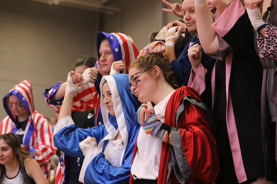 """The student section poses for a picture with wrapped hands and boxing robes, following the theme """"The Final Showdown"""" during halftime of the basketball game which ended in a 50-42 win over St. Teresa's Academy Saturday, Feb. 24."""