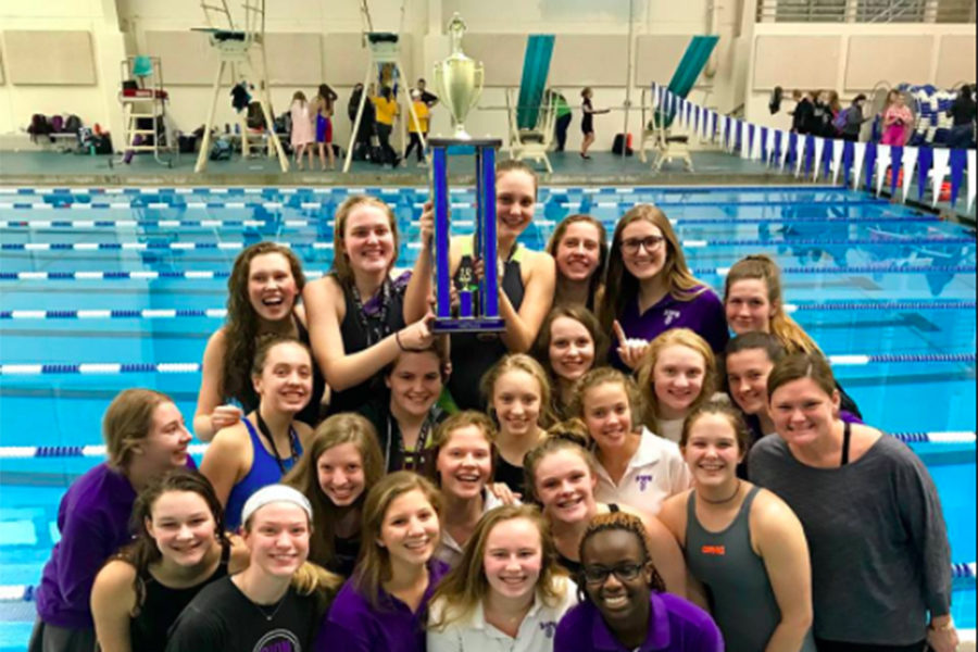 The+swim+team+poses+for+a+picture+with+seniors+Lexi+Smith+and+Ellie+Magsaman+holding+up+the+first+place+trophy+after+singing+the+school+song+to+celebrate+their+win+at+the+Independent+League+Championship.