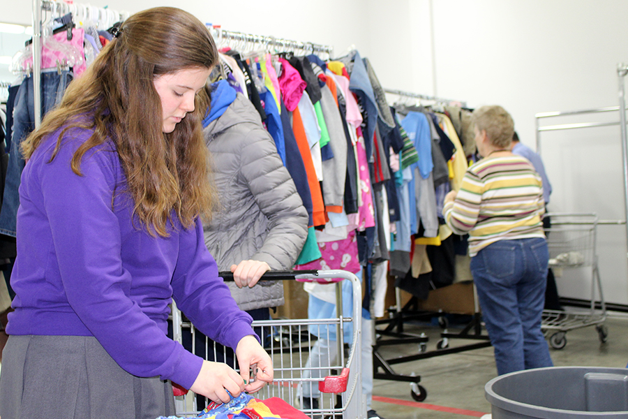 Freshman Mattie Mills puts tags on clothes to hang up for sale prior to opening day at Turnstyles March 7.