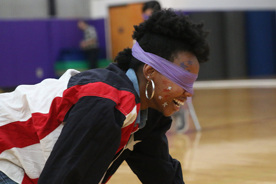 While competing in blindfolded musical chairs for Sion Olympics March 2, dressed in her grade's America theme senior Joileeah Worley laughs at herself as  she crawls around the gym floor looking for a chair.