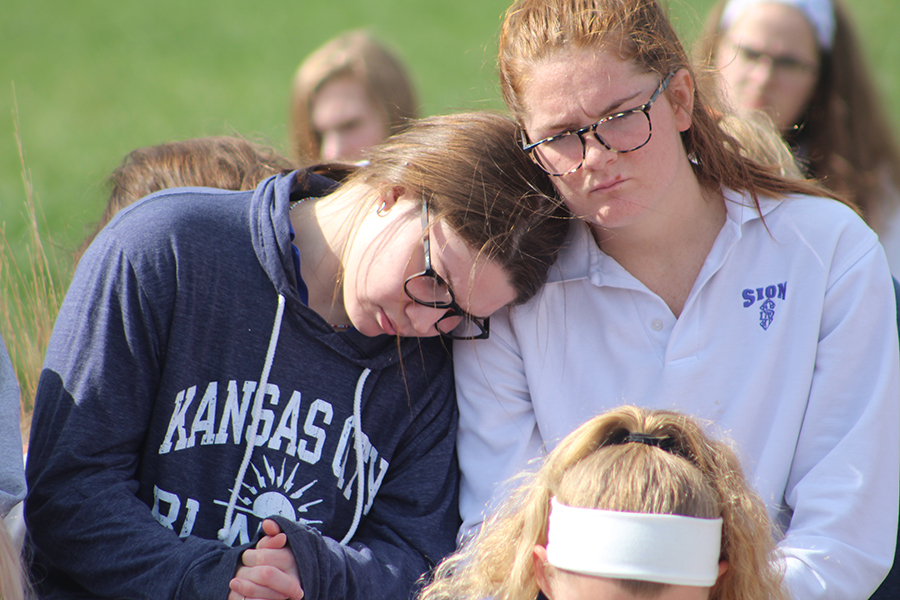 Senior Kate Sullivan leans on senior Aidan McEnerney's shoulder as they sit in silence to mourn those who have died at the hands of gun violence.