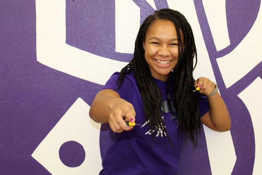 Junior Sade-Joy Dugbo poses with two screwdrivers she uses to build and fix the robot used for the high school's robotics competitions.