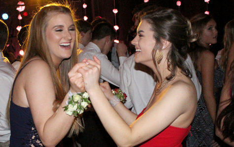 "While laughing, seniors Stella Lilek and Tierney Manning dance together at Prom April 7, 2018. The theme for Prom was ""In Bloom"" which was inspired by Gucci Mane's latest collection. This year's prom is Mar. 28. The theme is"