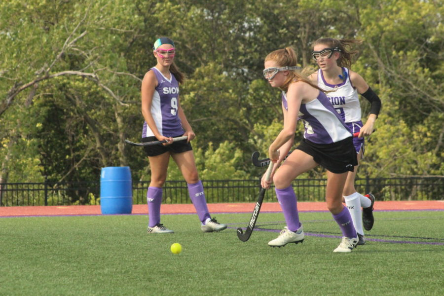 Freshman+Grace+Powers+hits+the+ball+away+from+junior+Lilly+Denney+during+the+Purple+and+White+field+hockey+scrimmage+Aug.+28.