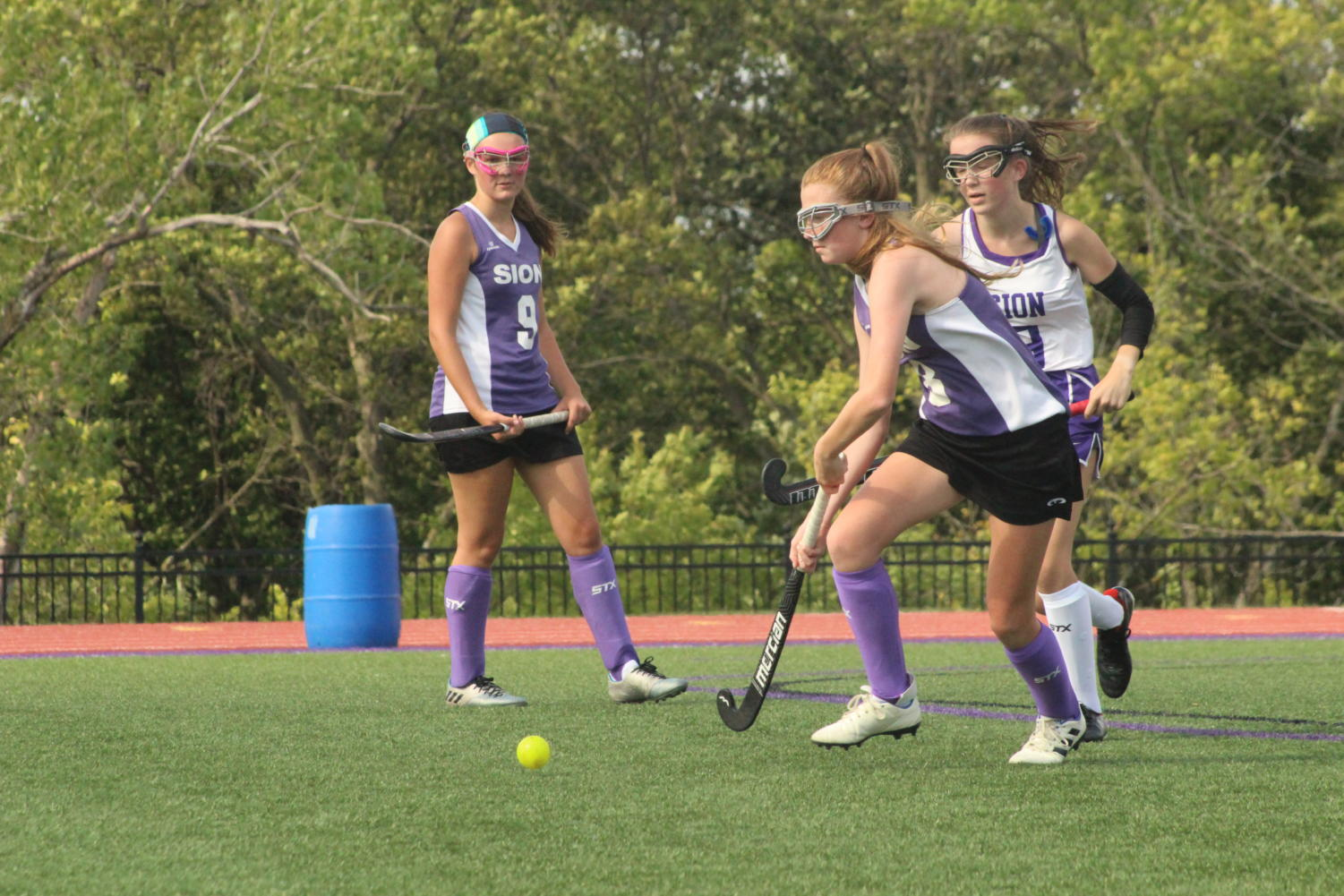 Freshman Grace Powers hits the ball away from junior Lilly Denney during the Purple and White field hockey scrimmage Aug. 28.