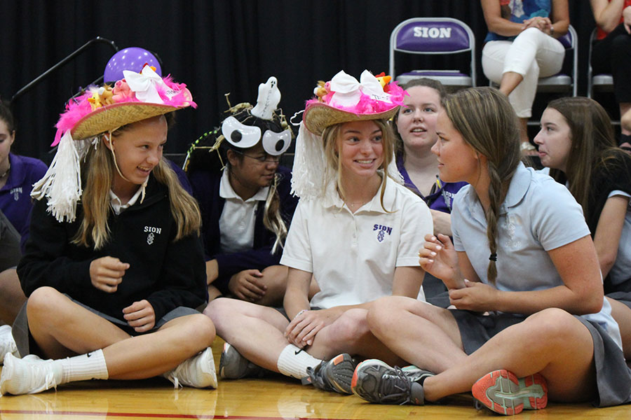 Senior Liz Oltjen introduces herself to freshmen Samantha Phillips and Tess Tappan after presenting them with their beanies at the beanie presentation Aug. 27.