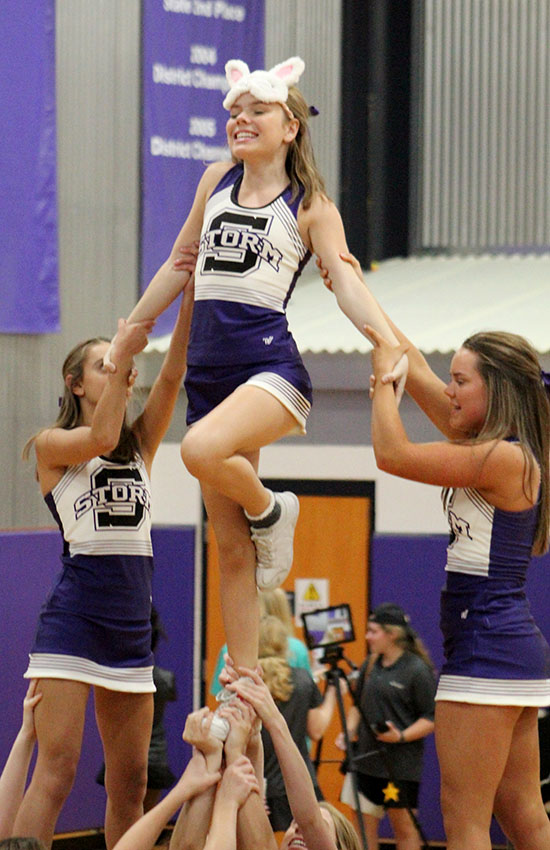 Sophomore Jane Oltjen stunts with the cheer team supported by sophomore Meg Wilkerson and senior Liz Oltjen at the volleyball game against St. Teresa's Academy Sept. 12. STA won in two sets.