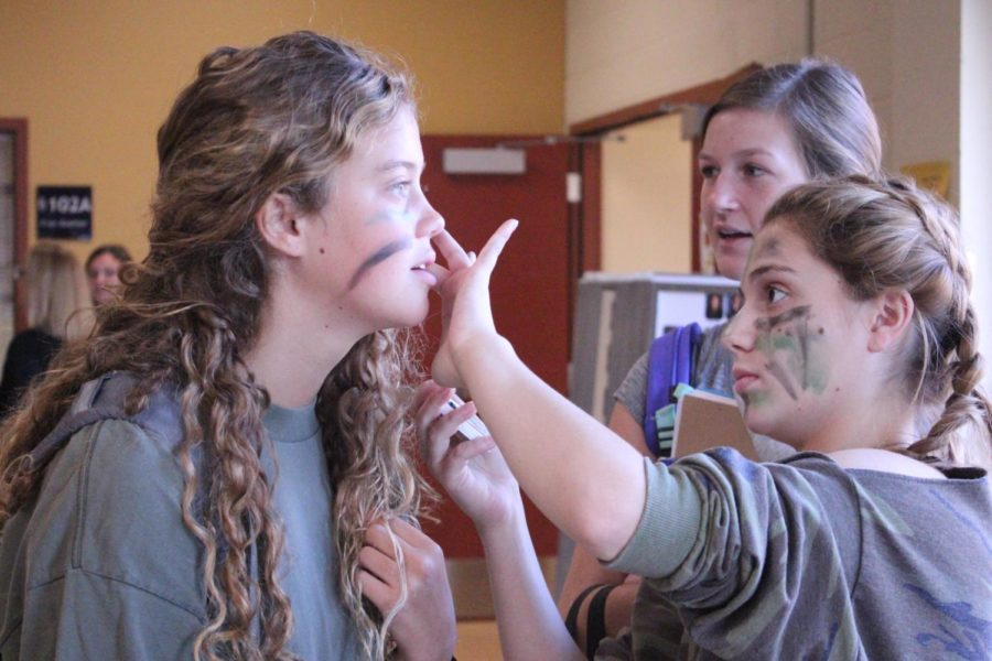 For the second day of spirit week, sophomore Lorelei Mathews paints camoflauge face paint on sophomore Ruby Wright before school Sept. 18.