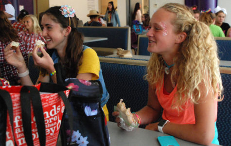 Sophomores Olivia Overlease and Grace Hill laugh while enjoying their lunch with their friends during spirit week in their Kidz Bop attire Sept. 19. The theme for the day was musical genres.