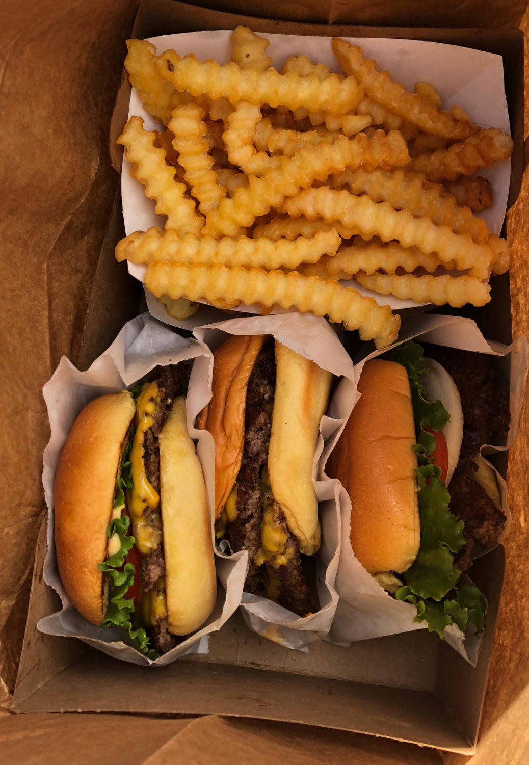 Shake Shack burgers and fries packed up to-go.