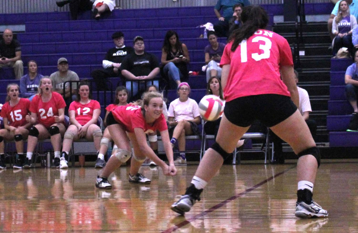 Freshman Bridgette Conner dives for the volleyball as junior Ceresa Munjak-Khoury goes to save it during the Dig Pink game Oct. 1.