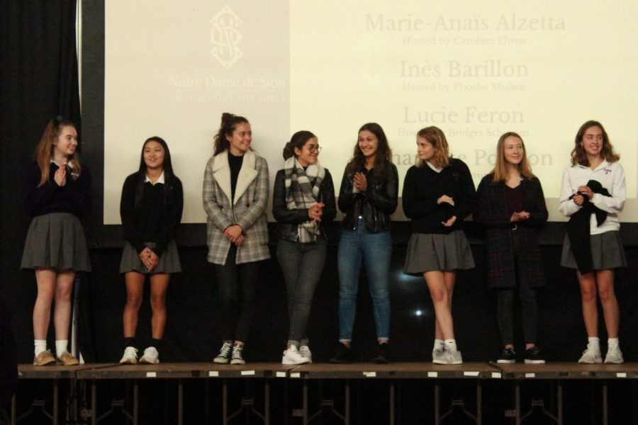 French Exchange students stand with their host sisters up on stage during the first quarter Grande Assemblee.