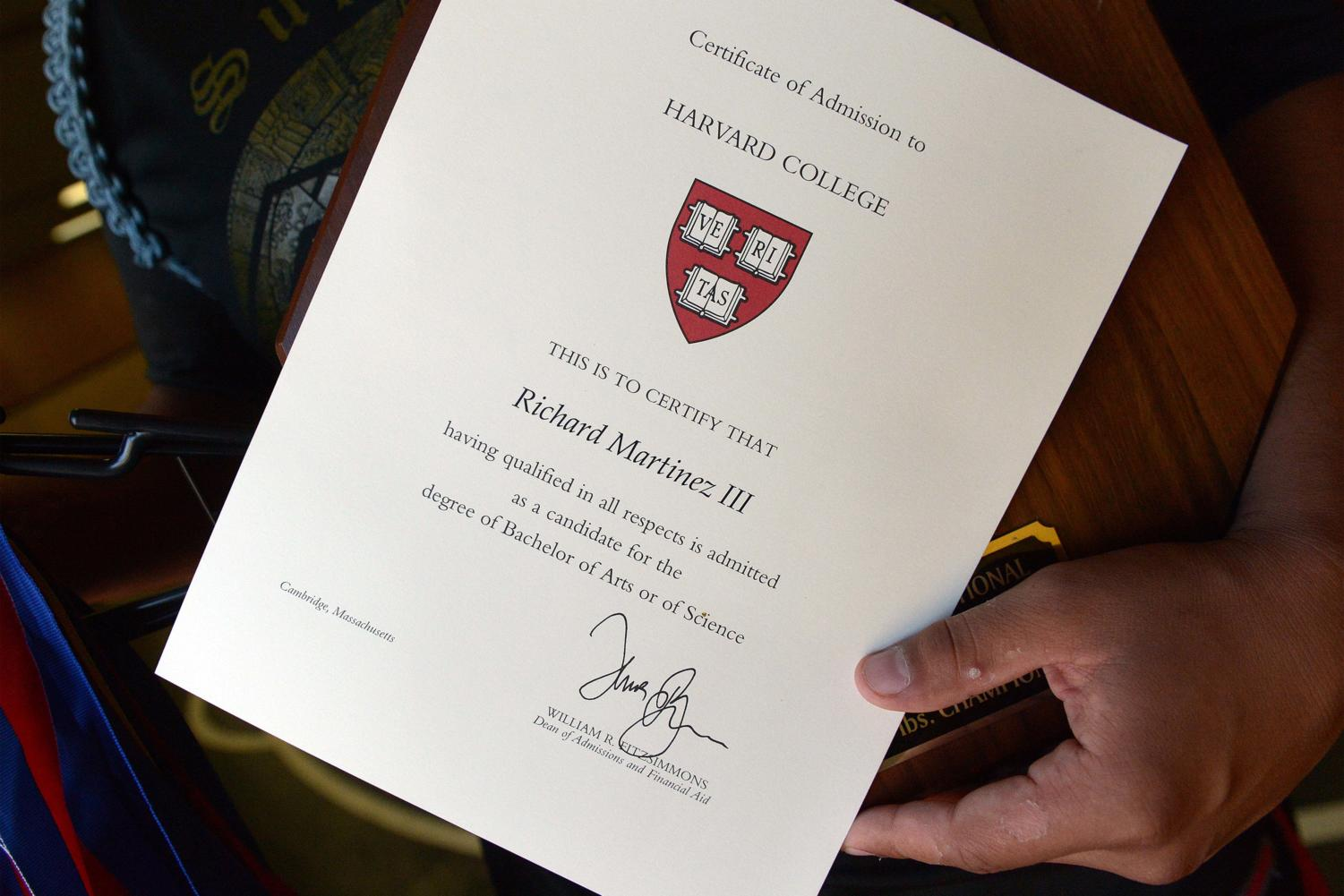 Richard Martinez III holds up a certificate showing his admission to Harvard, which he will attend in the fall, on Monday, June 13, 2017.  (Craig Kohlruss/Fresno Bee/TNS)