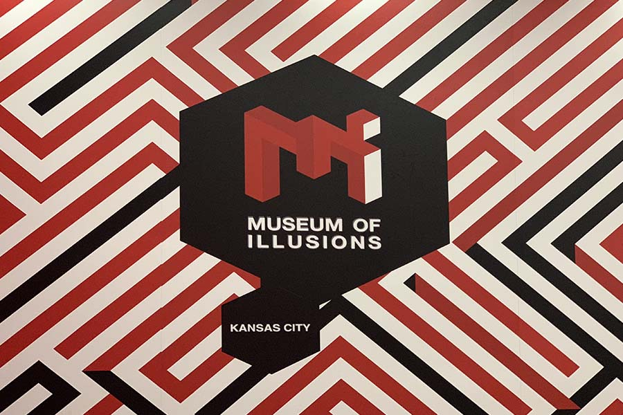 The Museum of Illusions Kansas City logo is displayed on walls throughout the museum.