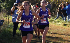 Senior Rose Orrick and alumna Brenna Richart '19 cross the one mile mark at the District cross country meet in Lake Jacomo Oct. 20, 2018. Orrick placed 35th and Richart placed 29th and will continue onto the sectional competition.