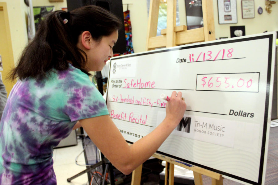 Tri-M president senior Sarah White signs a check of $655 for Safe Home after the benefit concert Nov. 13.