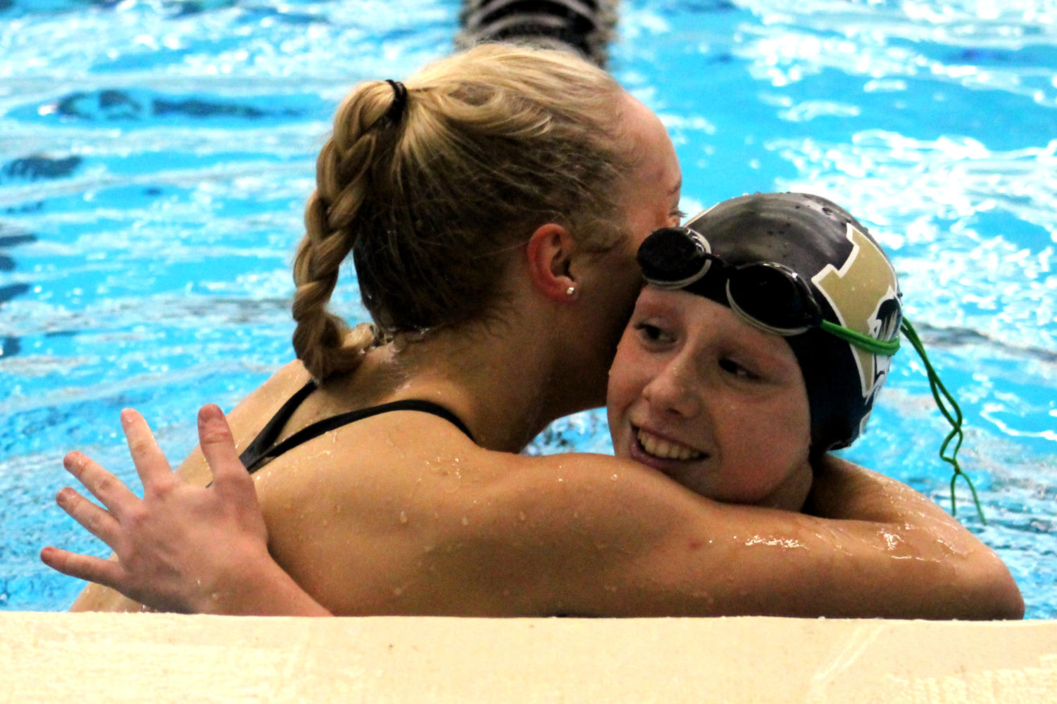 After qualifying for state in the 100-yard breaststroke, junior Olivia Townsend hugs Lee's Summit freshman Olivia Strikeleather who also qualified at the meet at Lee's Summit Aquatic Center Dec. 11.