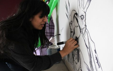 Senior Safa Khan works on her most recent addition to her collection of drawings on her wall, a character from Pan's Labyrinth.