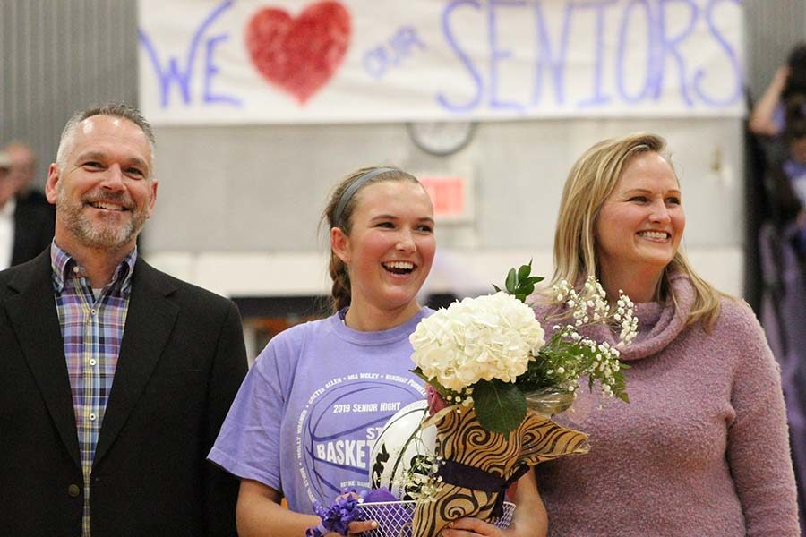 Senior Mia McLey stands with her parents Mike and Catherine to be recognized at the senior ceremony before the basketball game Feb. 21. McLey was recognized with fellow senior players Gretta Allen, Molly Wagner and Vanshay Purnell and senior manager Kaitlin Jones.