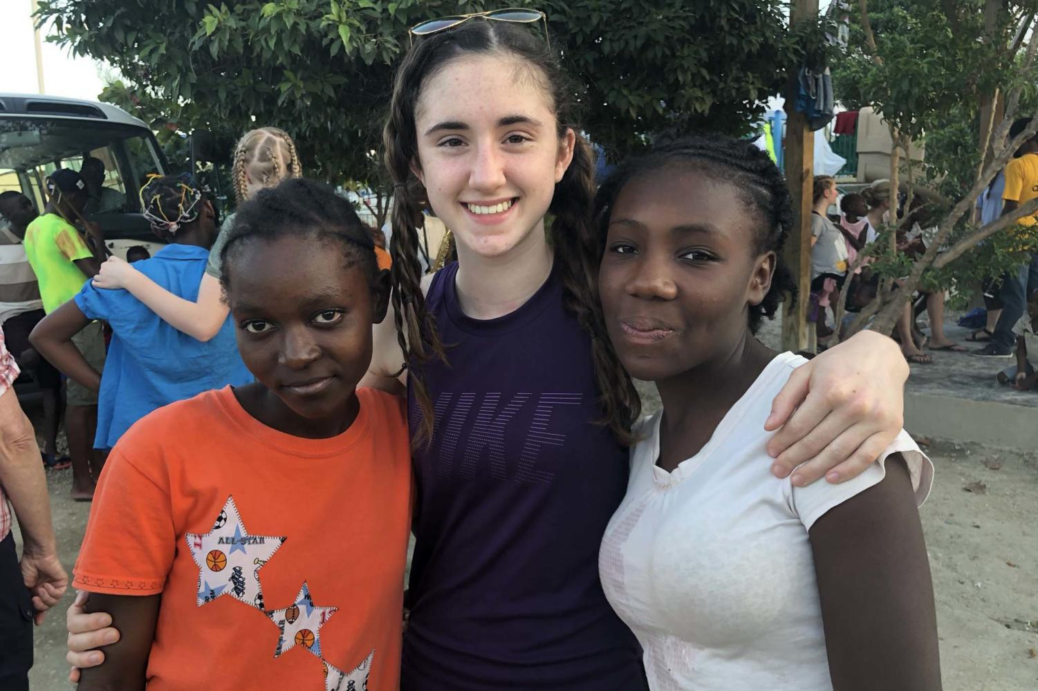 Sophmore Grace Hill hugs her new friends she has made while in Haiti volunteering with the Global Orphan Project.