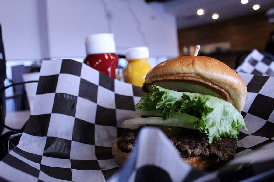 As single State burger is served on black and white plaid paper at Burger State.