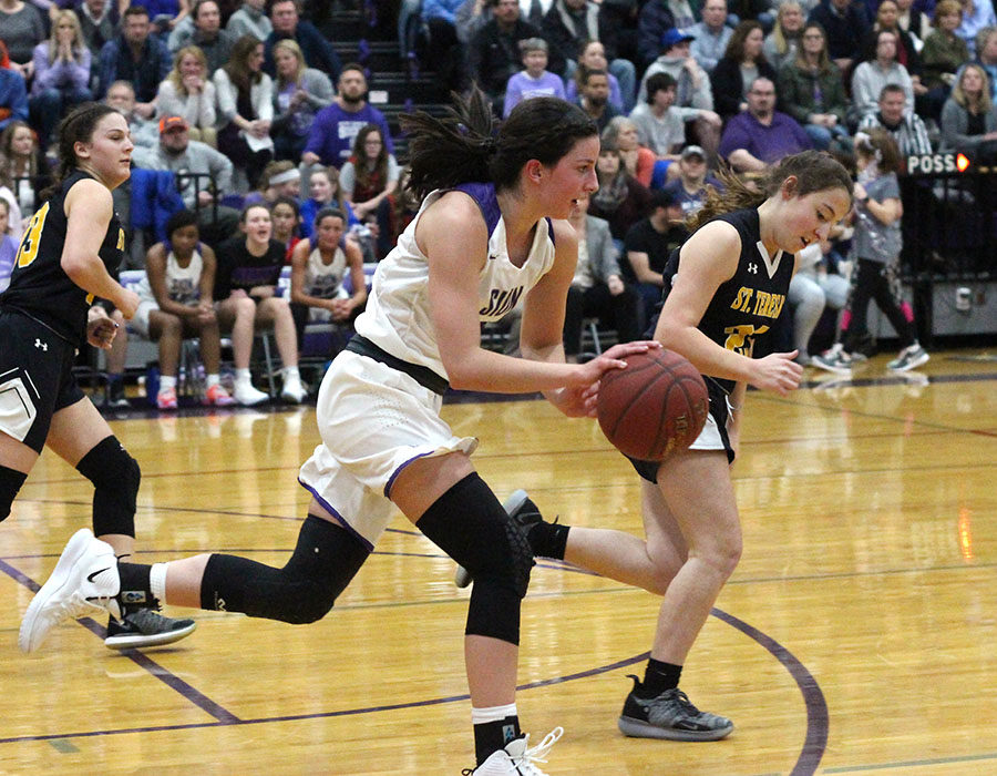 Sophomore Shannon Karlin rushes the ball down the court in the final seconds of the third quarter during the basketball game versus St. Teresa's Academy Feb. 21. The team fell to the Stars 61 to 55.