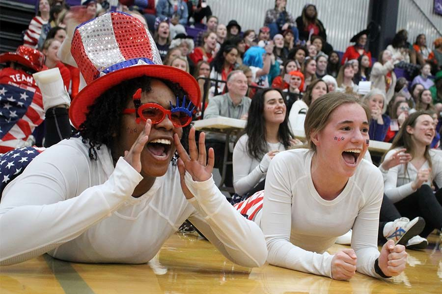 Seniors Kendall Rogers and Gabby Grimaldi cheer on seniors Lola Tebbe and Savannah Childress participating in a game of blindfolded musical chairs during Sion Olympics March 7. Junior Peyton Wiewel ended up winning the game.