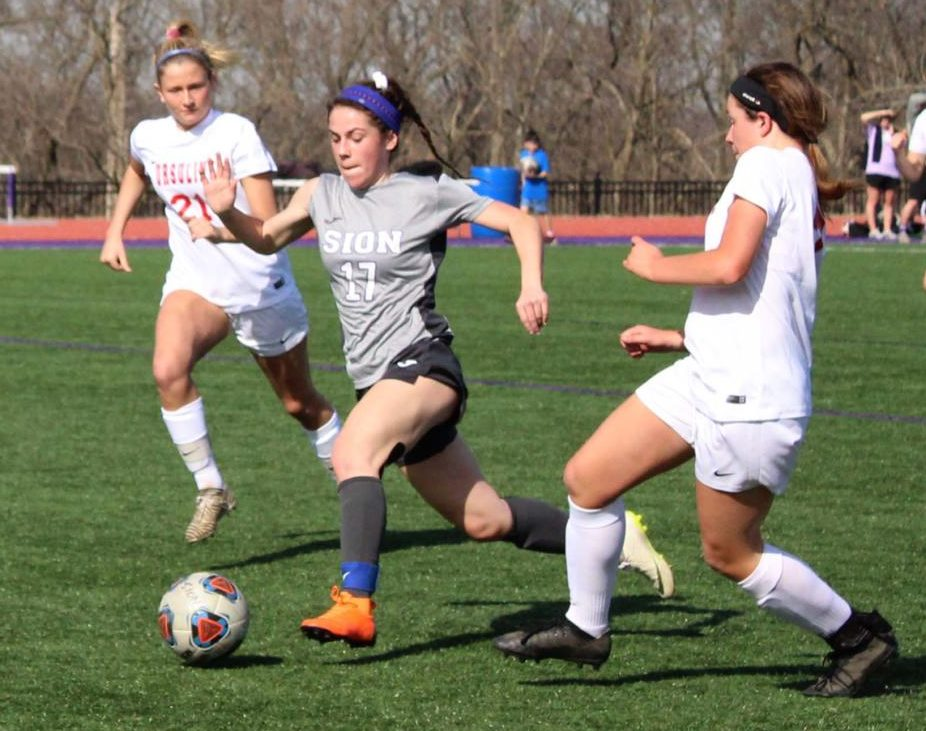 During the first home game against Ursuline Academy March 22, sophomore Kennedy Ruark dribbles through two defensive players, to make a shot on goal. The team won with a score of 3-1.