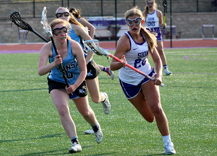 After saving the ball, sophomore Mikayla Gunther runs toward the goal while playing against Blue Valley High School at home March 27. The game ended in a loss for the team with a final score of 15-6.