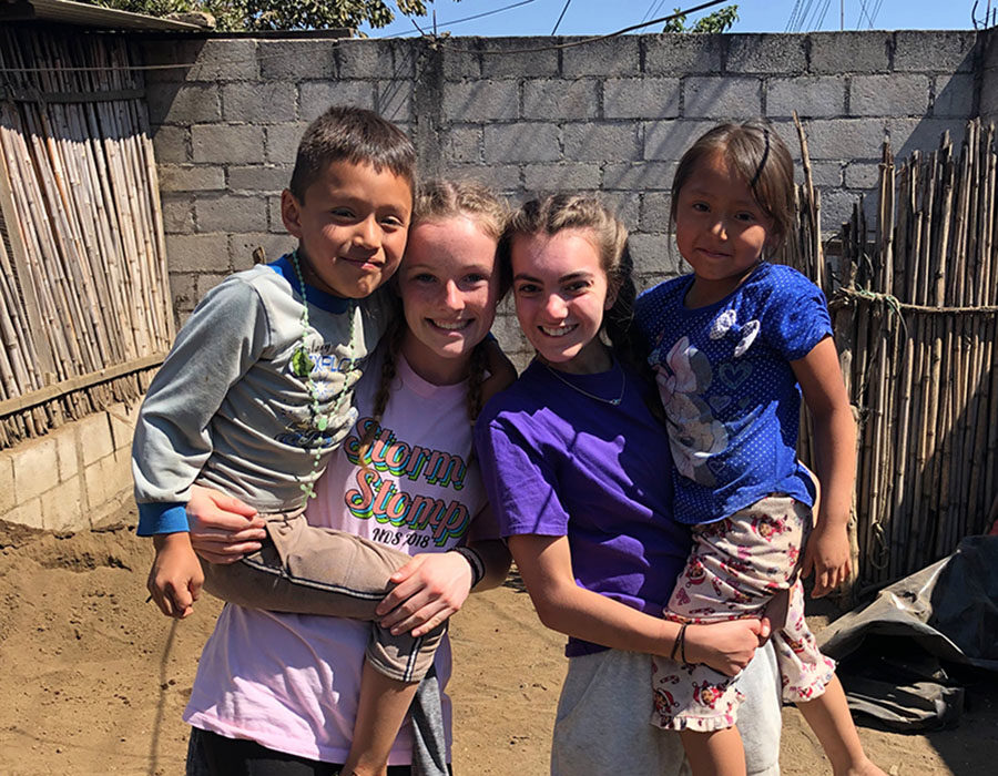 Alumna Molly Conway 19 and senior Meg Wilkerson hold Guatemalan children while working on building a concrete stove for the family in San Andres Itzapa March 11, 2019. This years trip to Guatemala has been postponed due to concerns surrounding the coronavirus.