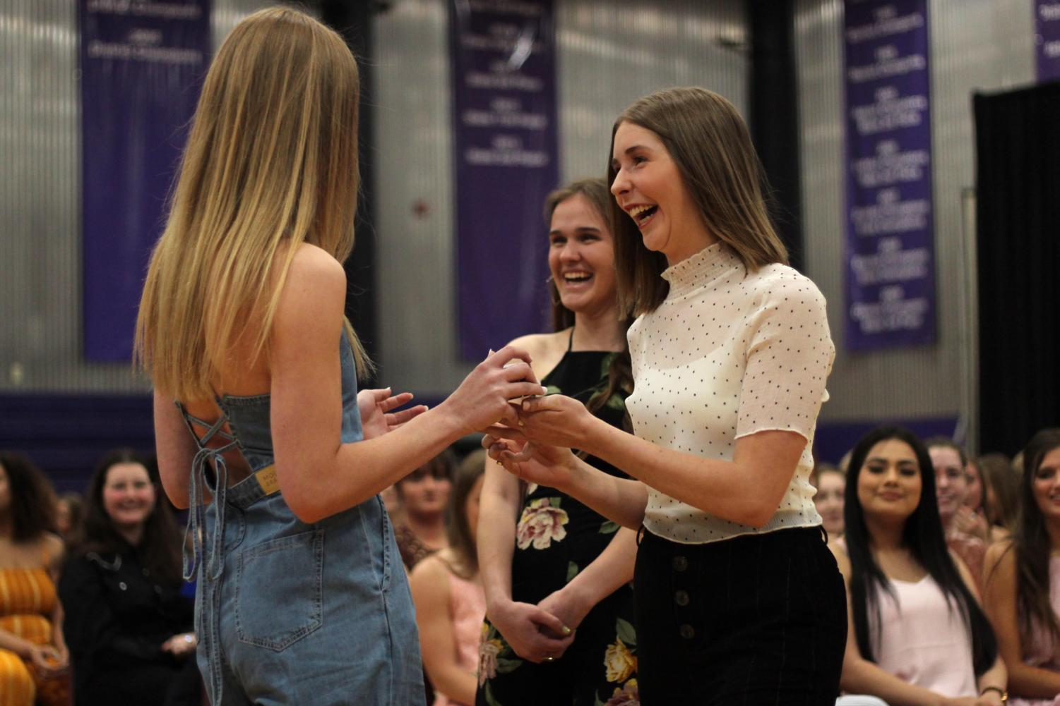 Seniors Emily Koca and Lily Muehlbach present junior Libby Slaymaker with her class ring at the junior ring ceremony April 11.