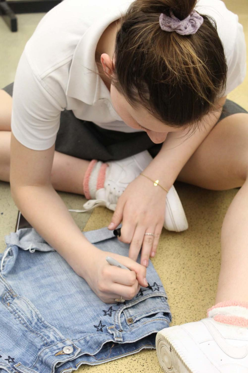 Junior+Ava-Grace+Vermillion+outlines+her+design+before+she+paints+white+stars+on+jean+shorts.%28Photo+by+Stephanie+Vince%29