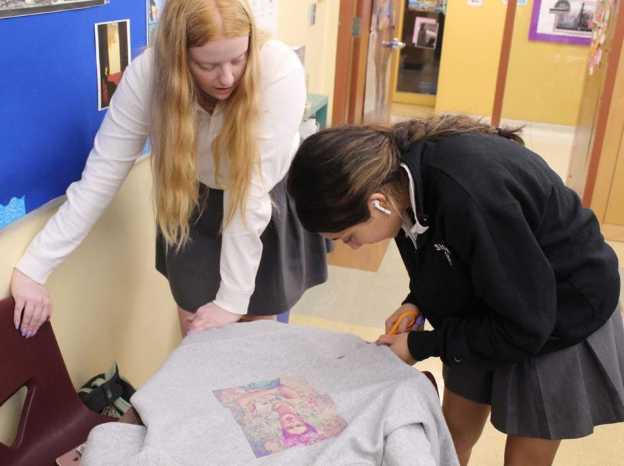 Sophomores Bella Aquino and Anna Gordon work together to crop and distress an old crewneck.