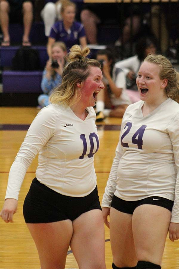 Seniors Caroline Garrison and Savannah Friedebach cheer after the Storm wins the point against St. Teresa's Academy volleyball team Sept. 12. The team lost in two games.